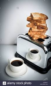 mound of toast balanced on top of toaster with cup of coffee
