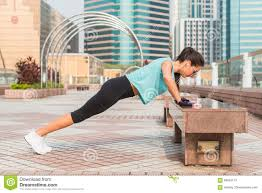 fitness woman doing feet elevated push ups on a bench in the city