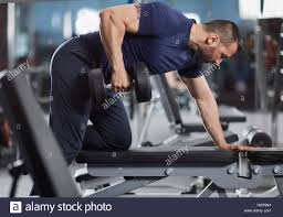 man doing dumbbell row for back workout in the gym stock photo