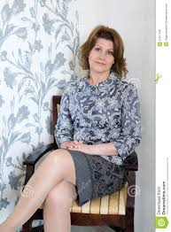 sitting chairs for living room middle aged woman sitting on chair in the living stock photo