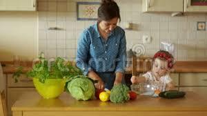 maman baise cuisine une mère prépare le dîner dans la cuisine coupe les