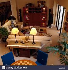 birdseye view of lighted lamps on console table behind beige sofa