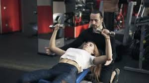 Dumbbell Exercises On Bench Young Bearded Coach Is Helping A Woman Lying On A Bench In A Gym