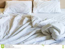 messy white bed sheets and white pillows after waking up stock