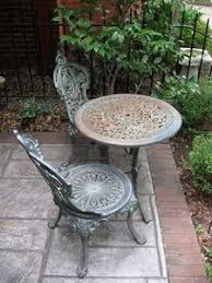 cast iron outdoor table wrought iron chairs with upholstered cushions at an outdoor seating