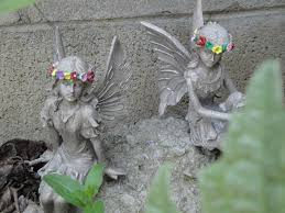 sitting fairy with legs crossed statue garden statues