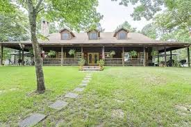 kountze log cabin boasts open floor plan lush landscaping