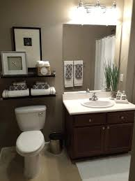 above toilet cabinet small brown tile floor and wall opulence