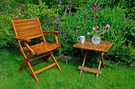a hardwood garden chair and table cup of coffe and a vase with
