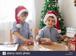 At Home Christmas Trees by Two Cute Boys With Santa Hat Preparing Cookies At Home Christmas