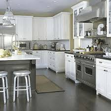 white kitchen cabinets with dark floors stainless steel