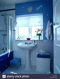 white blind on window above pedestal basin in blue and white