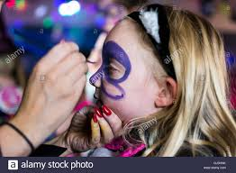 young having a butterfly painted on her face at a halloween