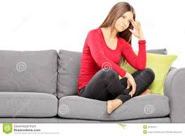 sad young woman sitting on a modern sofa royalty free stock