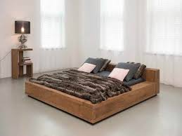 brown teak bed frame with black black blanket and grey pillows on