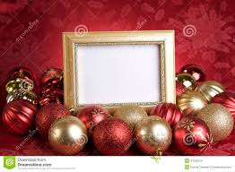 empty gold frame with christmas ornaments on a red background