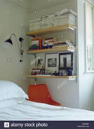 wall lamp beside bookshelves corner of bedroom above bed stock
