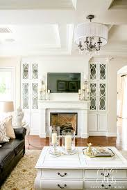 transitional home decor white family room with dark leather couches pretty chandelier and