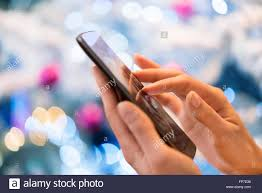 At Home Christmas Trees by Woman Using Her Mobile Phone At Home Boke Christmas Tree