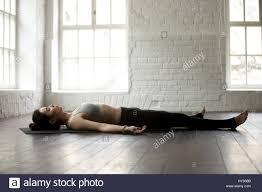 young attractive woman in savasana pose white loft studio backg