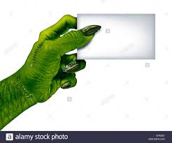 green halloween background zombie hand holding a blank card sign on a side view as a creepy