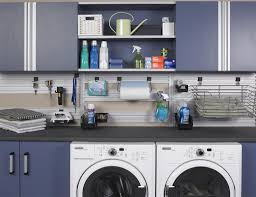 garage laundry room with fitted cabinets and white washer machines