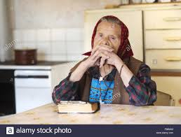 very old woman wearing head scarf is praying in her country style