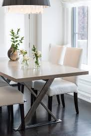 gray x base dining table with white leather chairs contemporary