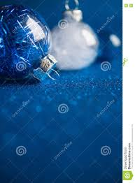 white and blue christmas ornaments on dark blue glitter background