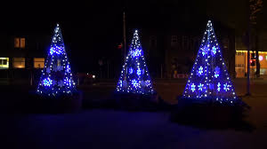 modern christmas tree form street decorations in city and cars
