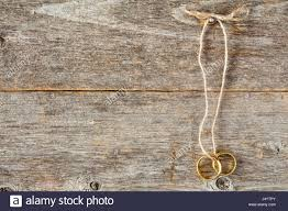 two gold wedding rings with string hanging on wooden wall