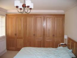 custom bedroom wall units light brown drapes black framed glass