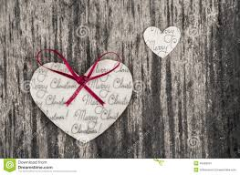 heart shaped paper christmas ornaments on a rustic wood background