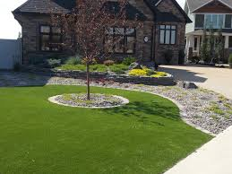 minimal maintenance front yard with artificial turf and a rock