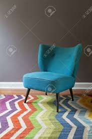 single teal blue armchair and colorful chevron pattern rug