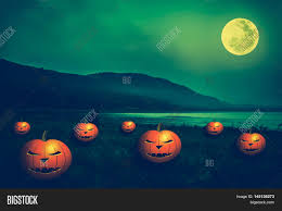 halloween scary background green mountain and beautiful full moon outdoors at night pumpkins with