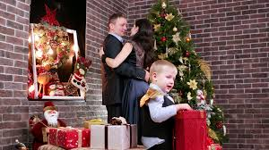 child playing with christmas gifts on the background lovers