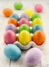 brightly colored speckled easter eggs sitting in ceramic egg