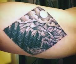 mountains and pine trees on forearm ink to inspire