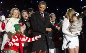 president obama joined by wife and their daughters as they light