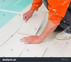 renovating a house handyman laying down laminate flooring boards stock photo