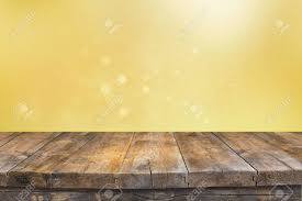 rustic wood table in front of glitter green and gold bright bokeh