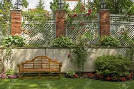 a garden wall with a trellis and red rose bushes stock photo