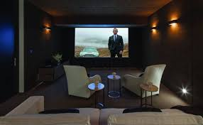 small home theater room with black walls and wall sconces small