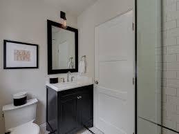 black bathroom vanity with black nailhead mirror transitional