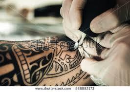 master tattooist makes tattoo on skin stock photo 721607992