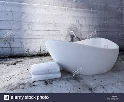 luxury freestanding bathtub in front of concrete wall stock photo