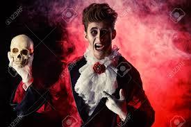 comic vampire holding a skull halloween dracula costume stock