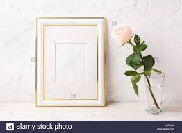 gold decorated frame mockup with tender pink rose in glass empty
