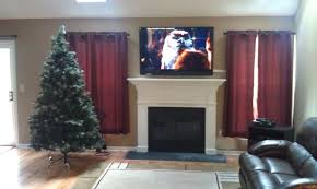 living room with white fireplace under wall mount tv stand added dark brown leather sofa with mounting tv above fireplace running cables plus tv in